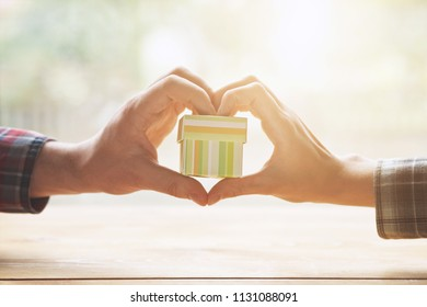 two loving hands making heart shape with gift box