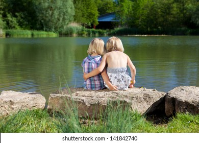 Two loving little sisters at the lake sitting with their arms around each other facing away from the camera on a rock on the shore