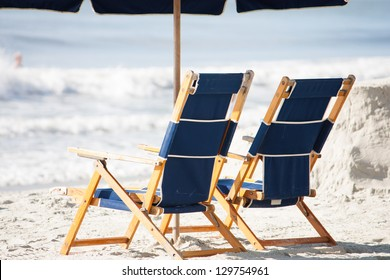 two luxury beach chairs sit under an umbrella on the sunny beach