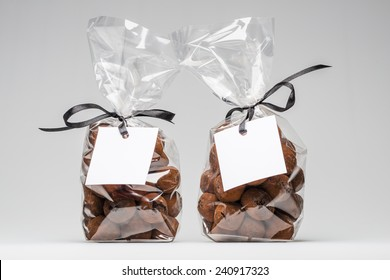 Two luxury plastic bags with elegant black ribbons of chocolate truffles for Christmas gift. Blank label and copy space. Shooting on white background in studio.