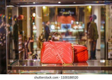 two Luxury red handbags, purse in store showcase in Milan, Italy. mannequins stand inside shop.