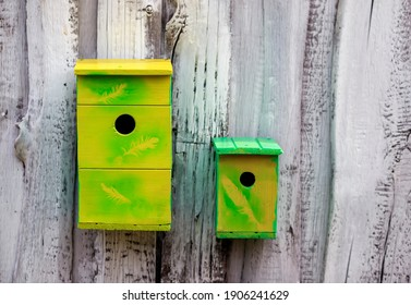 two made wooden and painted birdhouses hang on the white wall in the garden