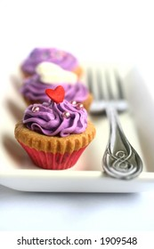 Two magenta icing covered cupcakes on white plate, isolated on white with a fork on the side