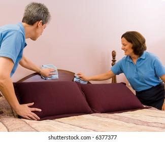 Two maids with pleasant expressions work dusting a headboard after making the bed.