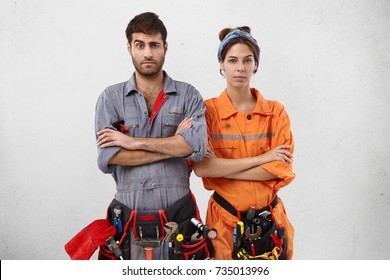 Two maintenance workers stand next to each other, keep hands folded, raise eyebrows in bewilderment, don`t know how to start repairing object. Female and male electricians have puzzled expressions