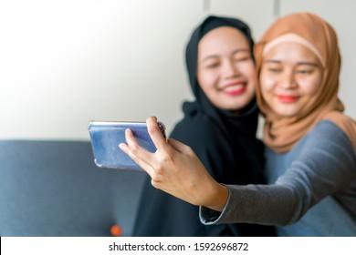 Deux amis malais portant le hijab sur le canapé avec leur smartphone prenant un selfie