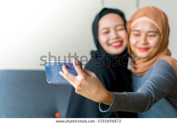 Two Malay friends wearing hijab at the sofa using smart phone taking selfie