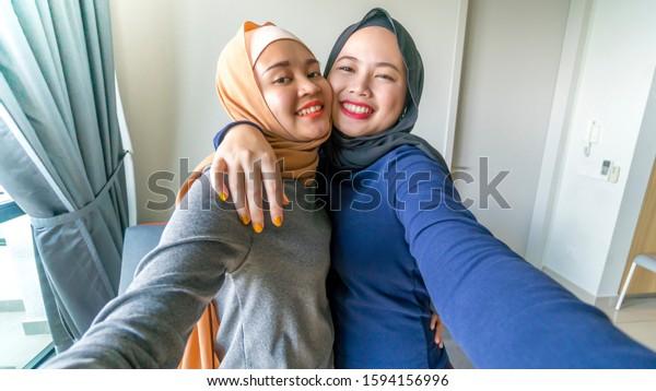 Two malay muslim girl wearing hijab smiling and having fun
