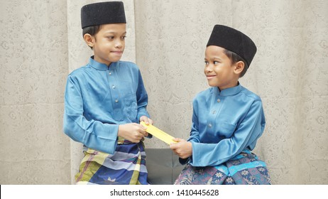 "Two Malay sibling exchange the money packet or ""duit raya"" during the celebration of Eid (Hari raya Aidil Fitri)"