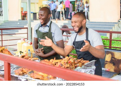 Two male African barbeque and roasted chicken sellers smiling and welcoming customers to patronize their business