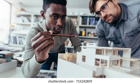 Two male architects in office discussing construction project. Young men working together on new building model.