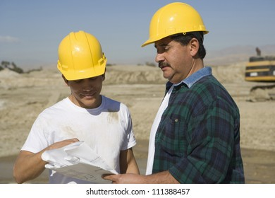 Two male architects wearing hard hat at construction site