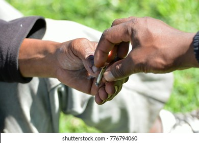 Two male black hands of South African men sharing a cigarette together in the park outside.