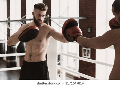 Two Male Boxers during Sparring on Boxing Ring. Muscular Black Man wearing gloves Punching Sporty Bearded Man in Red Boxing Gloves Pads during Boxing Exercise. Strength and Motivation Concept
