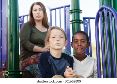 Two male children sitting on playground set with mother behind them
