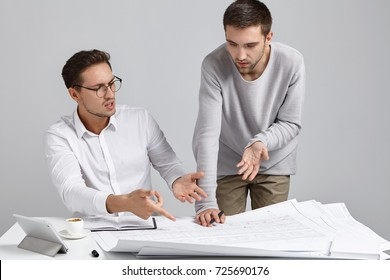 Two male colleagues architects having argument concerning architectural plan, expressing their points of view, gesturing actively, trying to persuade each another and prove that one is right