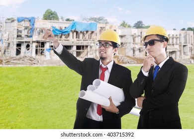 Two male contractor look at the residential construction and discussing together