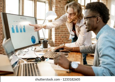 Two male coworkers working with analitycs in the beautiful office with brick wall on the background