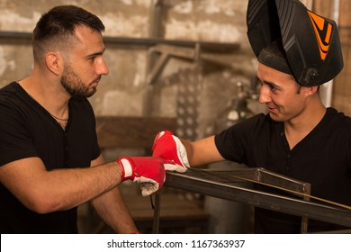 Two male craftsman, wearing in black shirt and protective gloves, looking at each other, discuss size metal frame, measuring by measuring tape. One man wearing in weld mask, lifting over face.