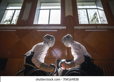 Two male disabled fencing athletes fight. men wear unbranded sports clothes
