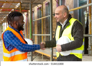 Two male engineers with safety jackets and hardhats reaching an agreement on construction site