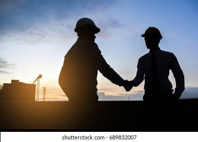 Two male engineers standing shake hands agreed to cooperate building construction.