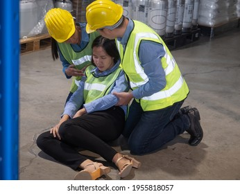 Two male and female colleagues are rescuing a female worker who is fainted from working inside a warehouse.