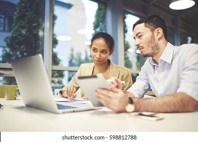 Two male and female marketing experts colleagues watching promo video for advertising campaign in social networks via laptop computer checking rate of popularity using application on touchpad and wifi