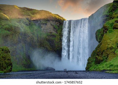 Two male and female tourists are walking at Skogafoss Falls in southern Iceland. In the morning, the sun rose from behind the mountains with green grass. This is a popular tourist destination.
