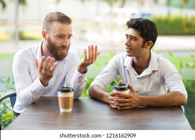 Two male friends drinking coffee and talking in outdoor cafe. People sitting at table with blurred view in background. Coffee break concept. Front view.