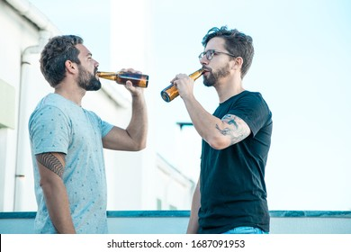 Two male friends enjoying beer on outdoor terrace. Two young men in casual meeting outside. Leisure time or beer party concept