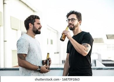 Two male friends enjoying party, chatting, drinking beer on outdoor terrace. Two young men in casual meeting outside. Beer party on terrace concept