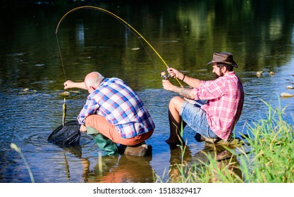 Two male friends fishing together. retired father and mature bearded son. happy fishermen friendship. fly fish hobby of men. retirement fishery. big game fishing. relax on nature. It is so big.