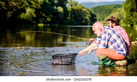 Two male friends fishing together. happy fishermen friendship.