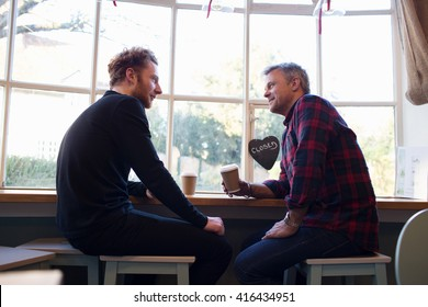 Two Male Friends Meeting In Coffee Shop