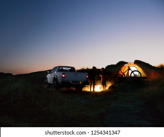Two Male Friends near Bonfire, Pickup Offroad Truck, Illuminated Tent and Bike at Night Camp in the Mountains. Bicycle Adventure and Car Travel Concept.