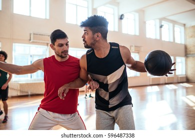 Two male friends playing a basketball together.