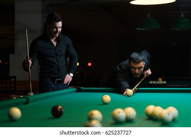 Two male friends playing billiard game in club