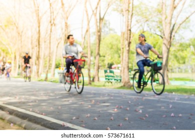 Two male friends riding their bicycles in the park.