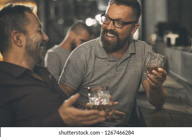 Two male friends spending time together in bar and having fun. Bearded men smiling, looking at each other and communicating. Men holding crystal glasses of whisky or scotch.