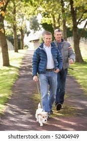 Two Male Friends Walking Dog Outdoors In Autumn Park Together