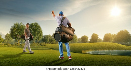 Two male golf players on professional golf course. Smiling golfers walking with golf clubs and golf bags