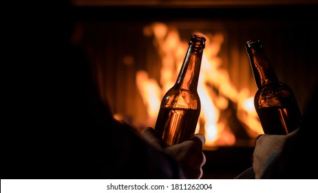 Two male hands with beer bottles on the background of the fireplace where the flame is burning