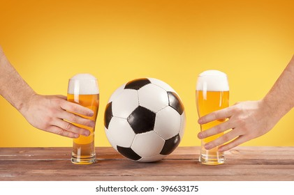 two male hands holding glasses of beer near soccer ball. Yellow background