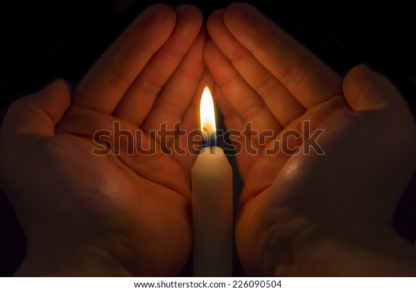 Two male Hands protecting the flame of a white candle on black background