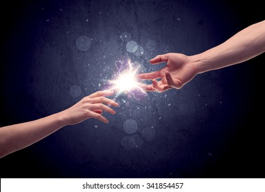 Two male hands reaching towards each other, almost touching with fingers, lighting spark in galaxy background concept
