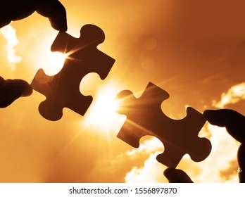 two male hands trying to connect couple puzzle piece with sunset background. Jigsaw alone wooden puzzle against sun rays. one part of whole. symbol of association and connection. business strategy.