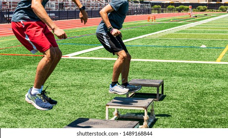 Two male high school track and field athletes doing box jumps on a green turf field during strength and agility practice.