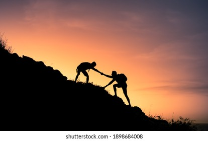 Two male hikers helping each other climb up a mountain. Teamwork and perseverance.