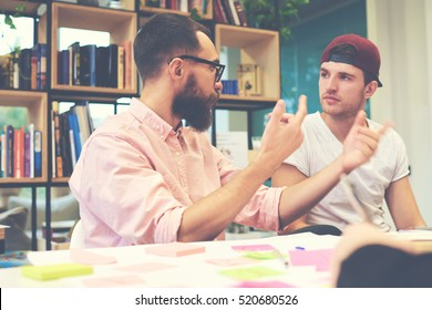 Two male hipsters architects sharing business thoughts ideas sitting in office.Young students preparing for making report by using special literature in library. Casual dressed teacher talk to pupil
